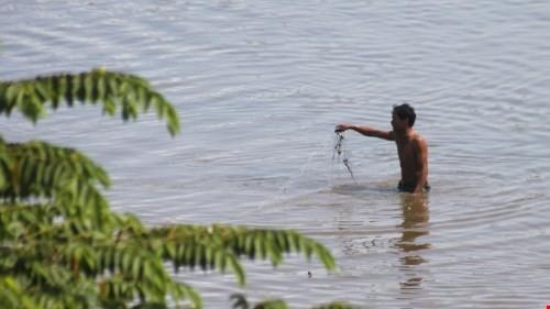Người dân bắt cá trong hồ nhiễm dioxin trong sân bay Biên Hòa - Ảnh: Tiểu Thiên