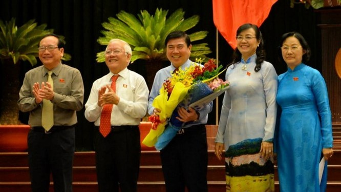 Chủ tịch UBND TP.HCM Nguyễn Thành Phong (giữa) nhận hoa chúc mừng từ ông Lê Hoàng Quân và bà Nguyễn Thị Quyết Tâm - Ảnh: Diệp Đức Minh