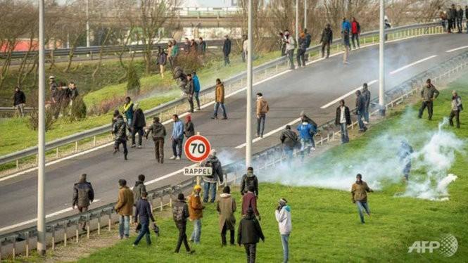 Cảnh sát Pháp dùng hơi cay giải tán đám đông những người di cư cố vào đường hầm để qua Anh - Ảnh: AFP