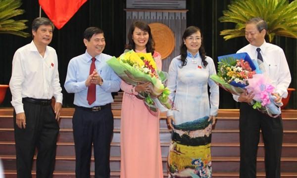 Hai tân Phó chủ tịch UBND TP Nguyễn Thị Thu (giữa) và Lê Văn Khoa (bìa phải) nhận hoa chúc mừng từ Chủ tịch HĐND TP Nguyễn Thị Quyết Tâm (thứ hai từ phải qua) và Chủ tịch UBND TP Nguyễn Thành Phong (thứ hai từ trái qua) - Ảnh: Hoàng Triều