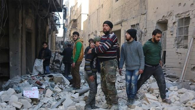 Người dân Syria đứng cạnh một tòa nhà bị hủy hoại ở thành phố Aleppo.