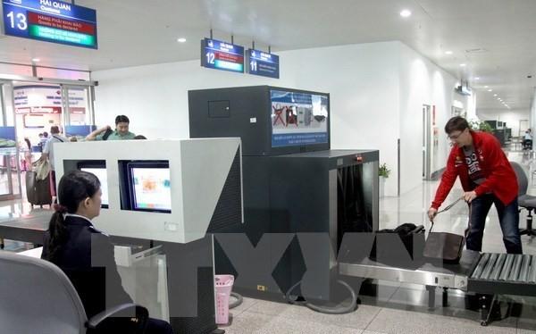 Nhân viên hải quan kiểm tra hành lý khách nhập cảnh qua hệ thống máy soi tại sân bay Tân Sơn Nhất. (Ảnh: Hoàng Hùng/TTXVN)