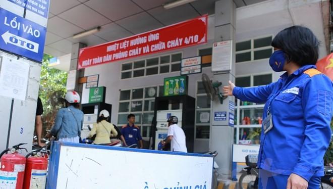 Nhân viên Petrolimex hướng dẫn khách hàng mua xăng trước khi điều chỉnh giá. (Ảnh: Đức Duy/Vietnam+)