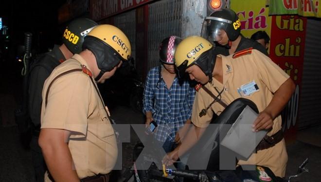 Lực lượng cảnh sát giao thông và cơ động kiểm tra phương tiện tại quận 12. (Ảnh: Mạnh Linh/TTXVN)