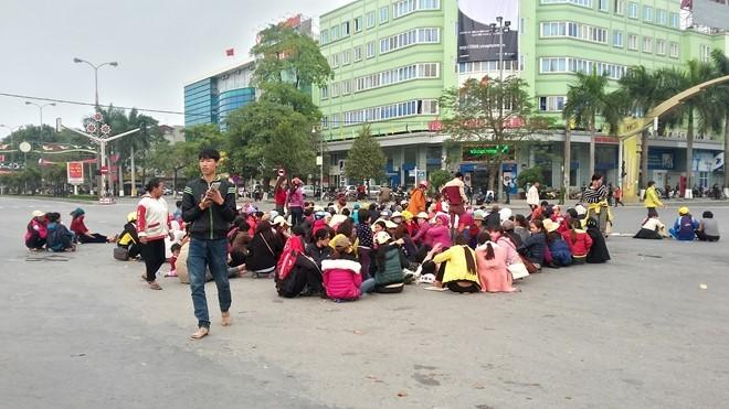 Người dân Sầm Sơn ngồi la liệt dưới lòng đường ngã tư đại lộ Lê Lợi - Trần Phú. Ảnh: Nguyễn Dương.