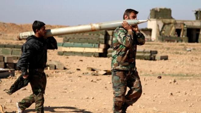 Binh sĩ chính phủ Syria vác rocket để bắn về phía lực lượng IS ở tỉnh Raqqa hôm 17/2. Ảnh: AP