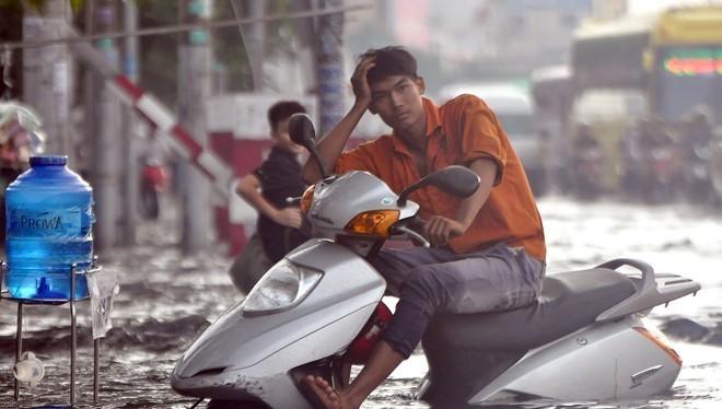 Thanh niên ngồi trên chiếc xe chết máy ngán ngẩm nhìn biển nước ở Sài Gòn. Ả nh: Lê Quân.