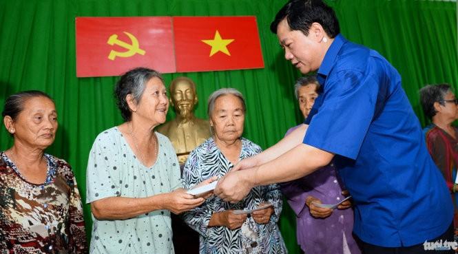 Bí thư Thành ủy Đinh La Thăng tặng quà cho các gia đình khó khăn ở xã đảo Thạnh An (TP.HCM) sáng 24-4 - Ảnh: Thuận Thắng