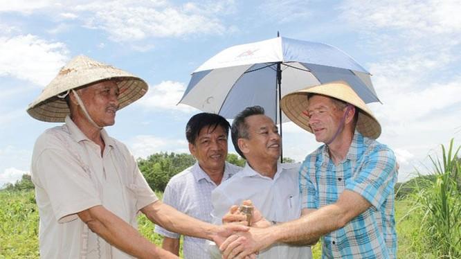 Ông Thomas nhận lọ đất đặc biệt từ ông Nguyễn Văn Thu (ngoài cùng bên trái) và ông Bùi Bác Văn.