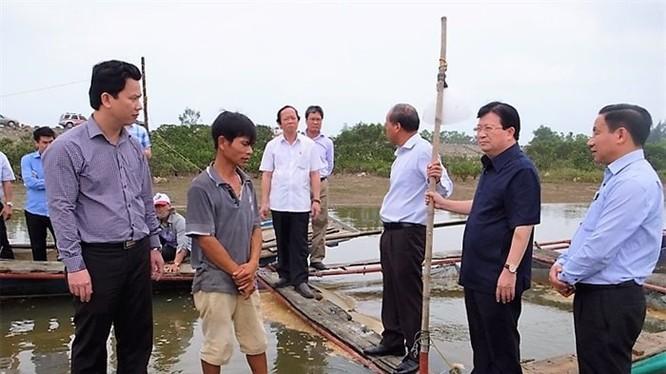 Phó Thủ tướng Trịnh Đình Dũng thăm hỏi động viên người dân nuôi cá lồng bè bị thiệt hại. Ảnh: T.Nga/PLO