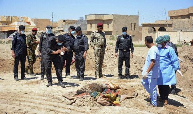 Lực lượng an ninh Iraq cùng nhóm điều tra pháp y xem xét một ngôi mộ tập thể chứa hàng chục thi thể đàn ông, phụ nữ và trẻ em tại sân vận động ở Ramadi, cách Baghdad 115km về phía tây - Ảnh: AP
