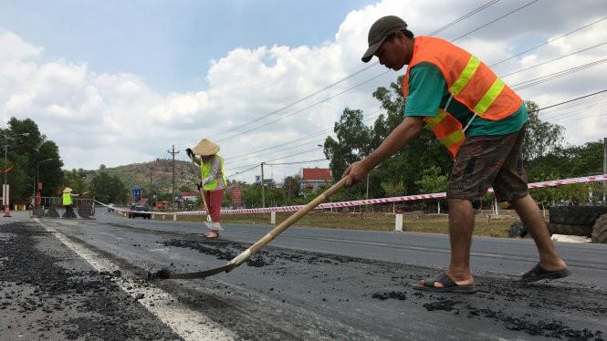 Chủ đầu tư Tổng công ty 319 cho nhân viên ra quốc lộ cào mặt nhựa đường bị trồi lên tại thị trấn Gia Ray, huyện Xuân Lộc, Đồng Nai - Ảnh: Hà Mi