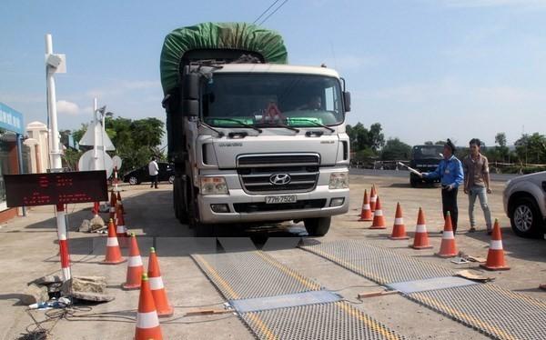 Lực lượng chức năng tiến hành kiểm soát tải trọng xe. (Ảnh: Sỹ Tuyên/TTXVN)