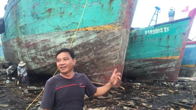 Ông Trà Văn Hoành bên tàu gỗ cỡ lớn đang bảo trì, sửa chữa định kỳ - Ảnh: MINH ĐỨC