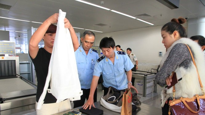 Nhân viên hải quan kiểm tra tư trang hành lý của hành khách tại sân bay quốc tế Đà Nẵng - Ảnh: Sa Sa
