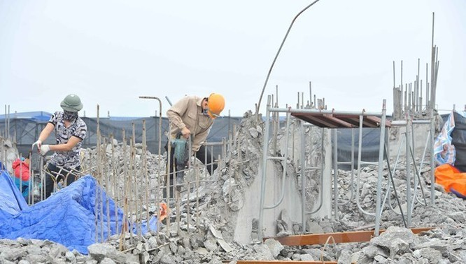 Công nhân tiến hành khoan, phá dỡ phần công trình xây dựng trái phép ở toà nhà số 8B Lê Trưc, Hà Nội, sáng 6/3. (Ảnh: Minh Đức/TTXVN)
