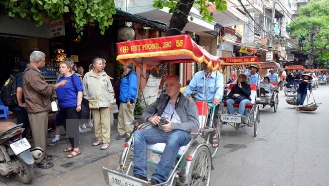 Du khách nước ngoài thăm phố cổ Hà Nội bằng xe xích lô. (Ảnh: Thanh Hà/TTXVN)