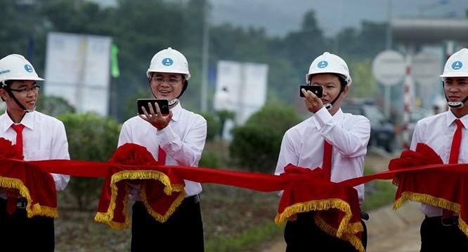 Những cán bộ ngành Giao thông tranh thủ chụp ảnh selfie bằng điện thoại thông minh trong khi đang nâng dải băng đỏ chờ cắt băng khánh thành cao tốc Nội Bài - Lào Cai vào tháng 9/2014.