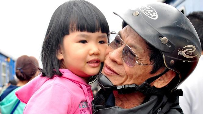 """Ông Trần Thẩm (70 tuổi, ngụ thị trấn Sông Vệ, huyện Tư Nghĩa) mừng vui ôm cháu ngoại theo mẹ vừa về cho thỏa nỗi nhớ mong sau một năm dài xa cách. """"Cuộc sống dẫu còn nhiều khó khăn nhưng mỗi dịp xuân về, vợ chồng tôi đều đi xe máy vượt hơn 15 km từ quê ra"""