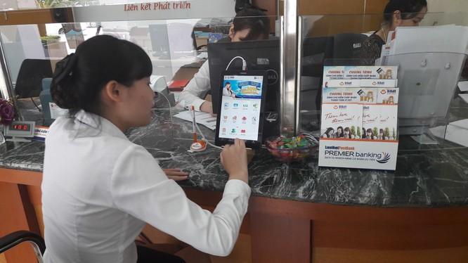 Nhân viên LienVietPostBank đang thực hành sử dụng máy tính bảng để giới thiệu cho khách hàng