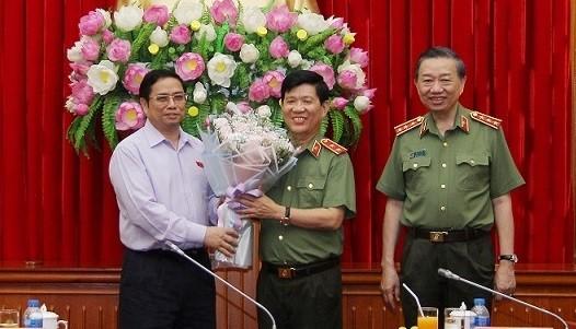Trung tướng Nguyễn Văn Sơn nhận hoa chúc mừng từ Trưởng Ban Tổ chức Trung ương Phạm Minh Chính. (Nguồn: mps.gov.vn)