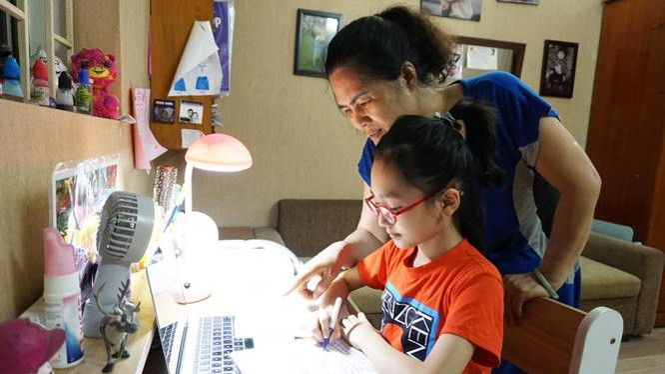 Phụ huynh trợ giúp con khi học trực tuyến - Ảnh: Hanoimoi.com.vn