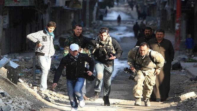 Các nhà báo mạo hiểm băng qua một con đường trong thành phố đang có chiến sự Aleppo ở Syria năm 2012 - Ảnh: Reuters