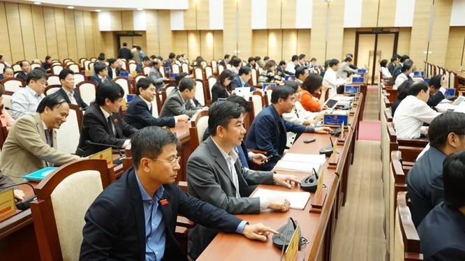 Các đại biểu bấm nút thông qua nghị quyết - Ảnh: Việt Bùi