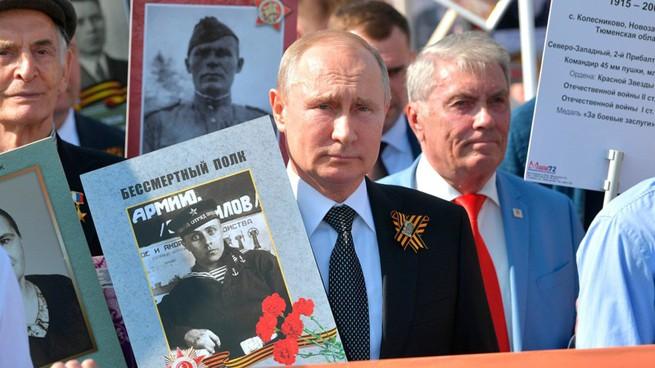 Tổng thống Nga V.Putin mang ảnh người Nga diễu hành cùng với Trung đoàn bất tử nhằm bảo vệ ký ức lịch sử về Ngày Chiến Thắng trong Chiến tranh giữ nước (Ảnh Sputnik)