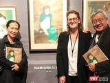 """Nhà nghiên cứu Ngô Kim Khôi (bên phải) cạnh bức tranh lụa """"Thiếu nữ cầm quạt"""" của họa sĩ Nam Sơn trưng bày tại Pháp"""