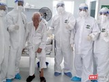 Cụ ông 83 tuổi (ngồi giữa ảnh) chiến thắng COVID-19, được xuất viện về nhà sau 2 tuần điều trị. Ảnh: BVCC