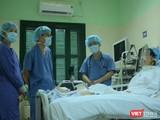 Bác sĩ giúp chị H. tập phục hồi chức năng tại giường (Ảnh: Quang Hùng)