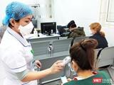 Nhân viên y tế đo nhiệt độ cho bệnh nhân.