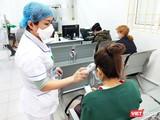 Nhân viên y tế đo nhiệt độ cho bệnh nhân (Ảnh - Minh Thuý)