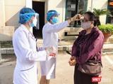 Nhân viên y tế kiểm tra nhiệt độ cho người dân trước khi vào bệnh viện (Ảnh - Minh Thuý)
