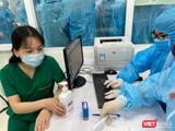 Nhân viên y tế kiểm tra hồ sơ, chuẩn bị tiêm vacicne phòng COVID-19 (Ảnh - Tuấn Dũng)