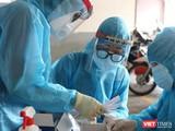 Lấy mẫu xét nghiệm trong vùng phong toả vì BN COVID-19 - Ảnh: HCDC