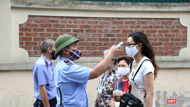 Bảo vệ đo nhiệt độ tất cả những người đến BV Việt Đức (ảnh: Nguyễn Hương)