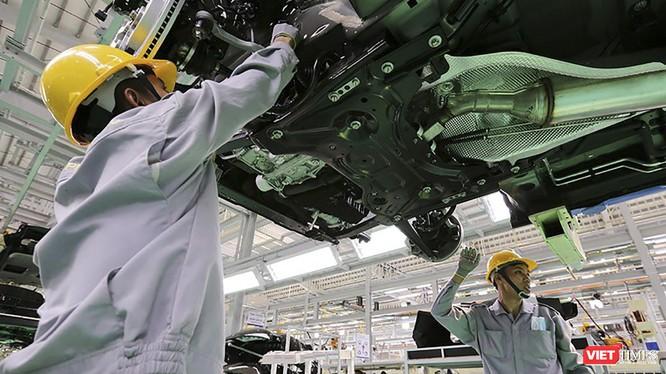 Công nhân làm việc trong phân xưởng lắp ráp ô tô.