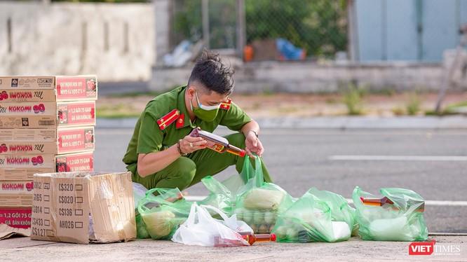 Chiến sĩ trẻ soát lại đơn hàng nhu yếu phẩm của người dân trước khi giao (Ảnh: Nghĩa Hiếu)