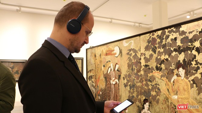 Khách thăm quan xem thông tin tác phẩm trên app iMuseum VFA tại Bảo tàng Mỹ thuật Việt Nam