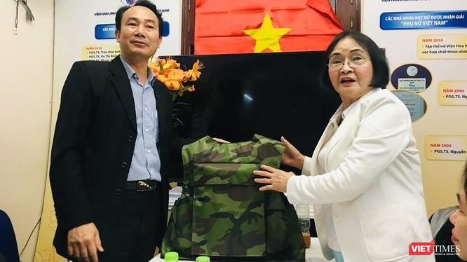 Đại diện Z117 và PGS.TS. Nguyễn Thị Hòe giới thiệu chiếc áo chống đạn sẽ được sử dụng sơn chống đạn và sơn chống cháy. (Ảnh: T.H)