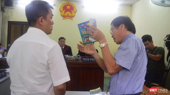 Họa sĩ Lê Linh (áo trắng) và ông Nguyễn Vân Nam (người đang cầm cuốn sách) - đại diện cho công ty Phan Thị với những trao đổi gay gắt tại tòa