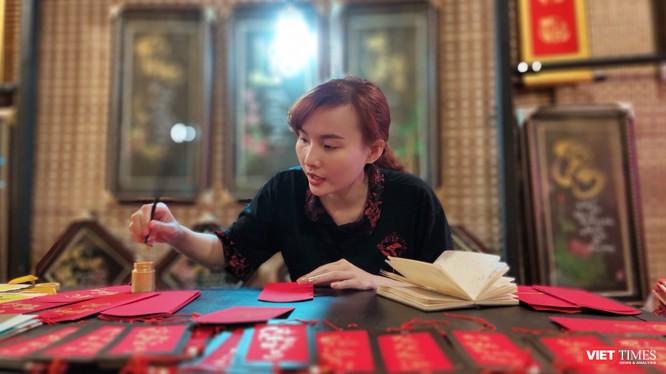 Một nữ thư pháp gia còn rất trẻ đang cho chữ tại phố ông đồ trước Nhà văn hóa Thanh niên