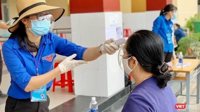 Kiểm tra trước khi tiêm chủng cho người dân - Ảnh: HCDC