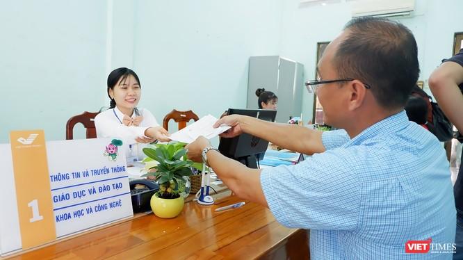 Người dân làm thủ tục hành chính công tại điểm giao dịch bưu điện. Ảnh: Kiều Minh.