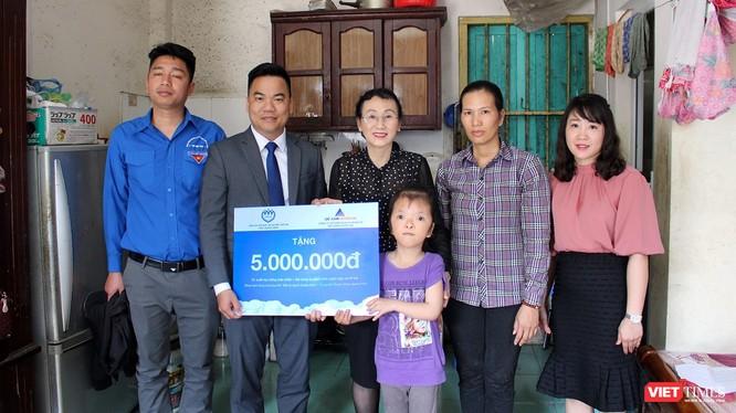 Em Lê Thị Trà My và gia đình nhận phần quà hỗ trợ dành cho trẻ em khuyết tật tiêu biểu. (Ảnh Hương Sen).