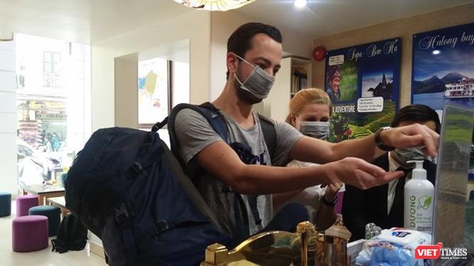 Người nước ngoài thực hiện sát khuẩn tay tại một khách sạn ở Hà Nội.