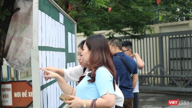 Học sinh và phụ huynh xem lịch thi. Ảnh: Minh Thúy