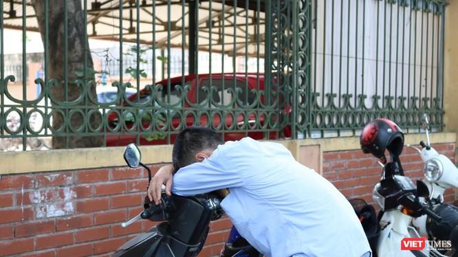 Một phụ huynh ngủ gục trong lúc chờ con thi xong. Ảnh: Minh Thúy.